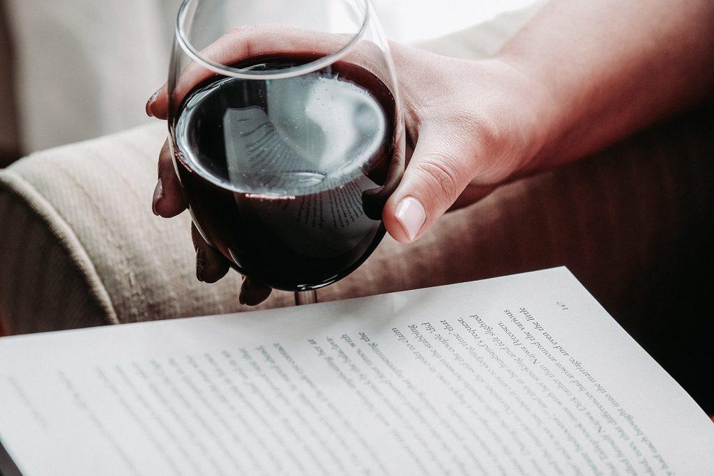Copo com vinho do Porto e livro sobre vinhos