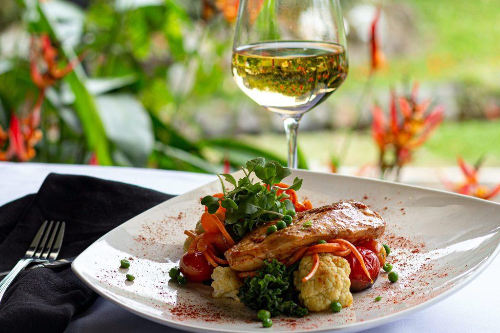 Copo de vinho branco com prato de peixe ou prato de carne e legumes